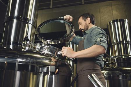 Brewer inspecting tank Foto de archivo