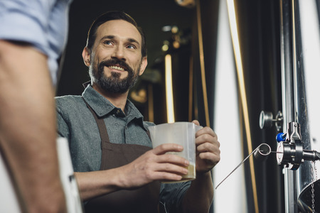 Brewer holding jug with  beer Stock Photo