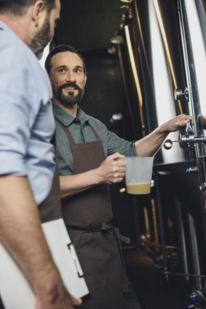 Brewery worker pouring beer Foto de archivo