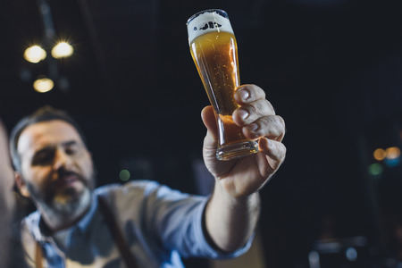 Brouwerijarbeider met een glas bier Stockfoto - 82277627
