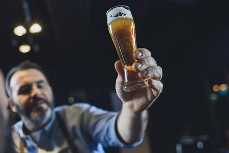 Trabajador de fábrica de cerveza con vaso de cerveza Foto de archivo - 82277627