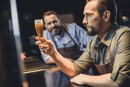 ビールのグラスとビール醸造所の労働者