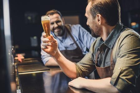 Cervecería trabajador con un vaso de cerveza Foto de archivo - 82277632