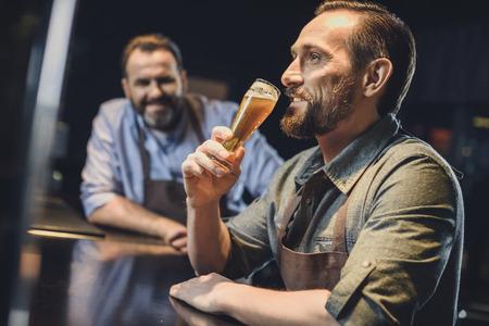 Brouwerijarbeider met een glas bier Stockfoto - 82277633