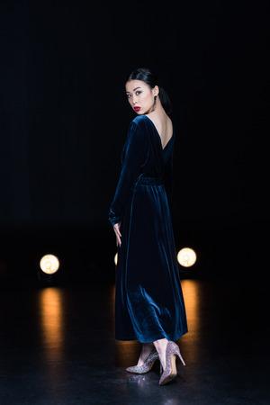 asian woman in maxi dress looking at camera