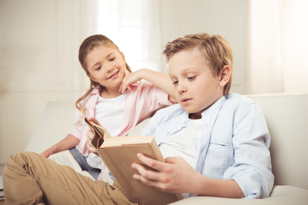 caucasian sister and brother reading book together at home Reklamní fotografie