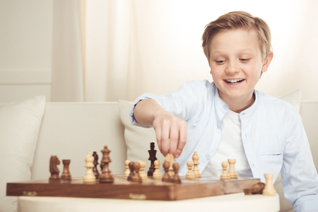 cheerful little boy playing chess alone at home Banco de Imagens