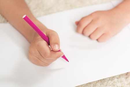 kid drawing with felt pen on blank paper sheet