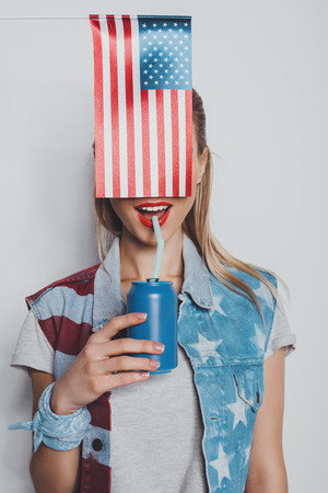 cheerful stylish girl in american patriotic outfit drinking soda from can, with american flag in front of her face isolated on grey Stock fotó