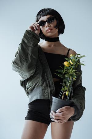 stylish woman in bomber jacket holding lemon tree in hands Stock Photo