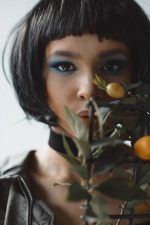 stylish woman with lemon tree looking at camera Stock Photo