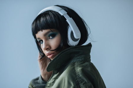 confident woman in headphones looking at camera