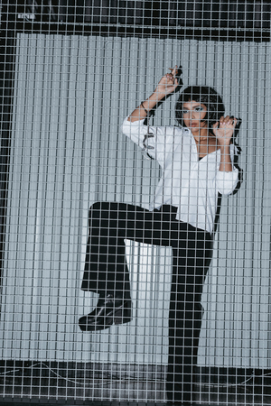 woman in white shirt with cuffs standing behind grate Stock Photo