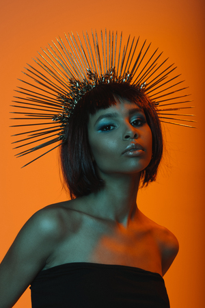 african american girl in headpiece with needles looking at camera Stock Photo