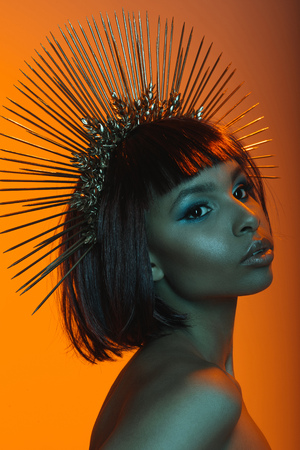 stylish african american woman posing in headpiece with needles Stock Photo