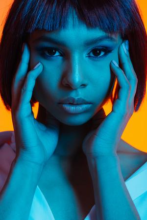 カメラ目線の顔に手で魅力的なアフリカ系アメリカ人女性 写真素材