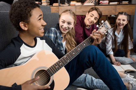 african american boy playing acustic guitar and singing while his friends listening at home