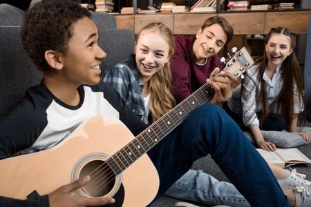 Afroamerikanerjunge, der Akustikgitarre spielt und singt, während seine Freunde zu Hause hören