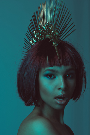young astonished african american woman in stylish headpiece