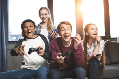 feliz multicultural adolescentes jugando videojuegos con joysticks en casa