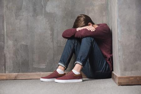 teenage boy sitting on floor with head in hands