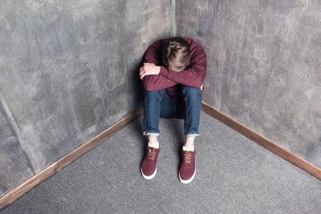 depressed teenage boy sitting on floor