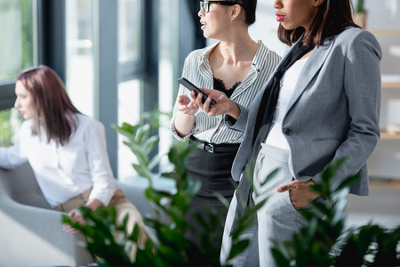 businesswomen standing and using smartphone with colleague sitting behind