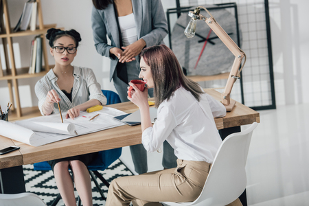 african american woman: professional young architects working with blueprints in modern office Stock Photo