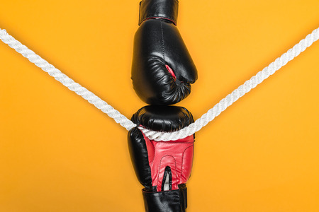 Black boxing gloves ready to fight with rope in the middle isolated on yellow Stock Photo
