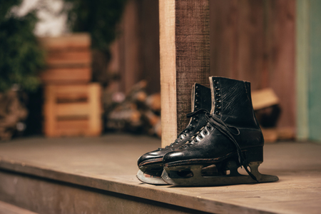 Closeup view of black old ice skates lying on wooden porch