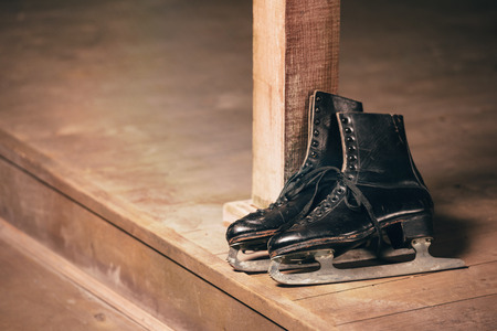 black old ice skates lying on wooden porch