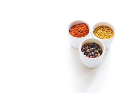 Close-up view of assorted aromatic dried spices in ceramic bowls