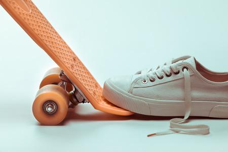 stepping: white sneaker stepping on hipster skateboard Stock Photo