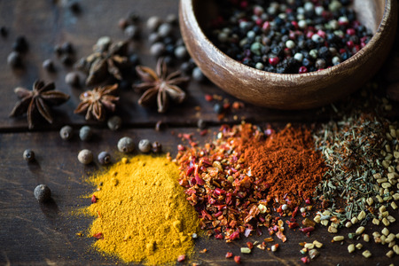 different kinds of pepper in bowl and spices with herbs scattered
