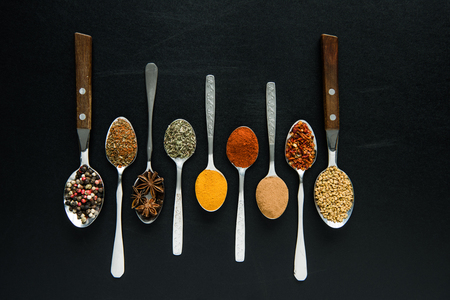 various spices and herbs in metal spoons isolated on black