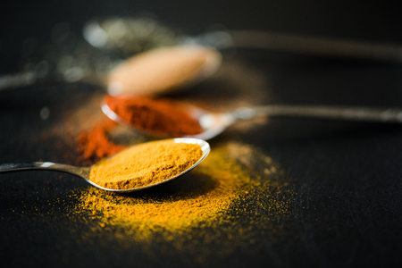 various spices and herbs scattered in metal spoon Stock Photo
