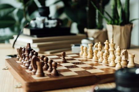 Een zwarte pion die tegen een volledige set schaakstukken blijft Stockfoto