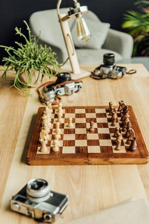 古いビンテージ カメラと本設定チェス盤のハイアングル