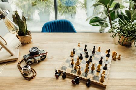 チェス チェス盤、ビンテージ カメラ、緑の植物を設定