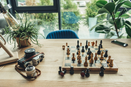 workplace concept with old retro camera, chess board and chess pieces