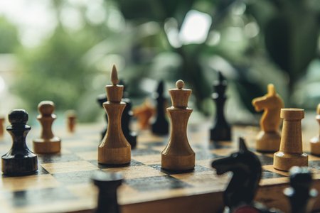 Closeup view of black and white chess figures on chess board