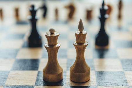 チェスボード上の白いチェス王と女王フィギュア