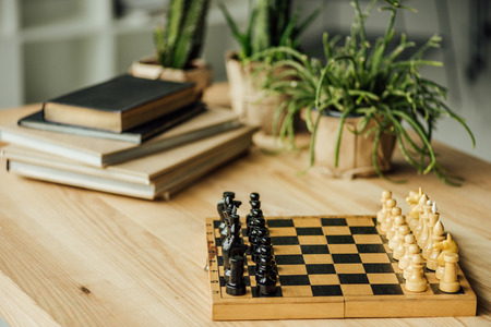 Chess board set for a new game on the table with books and potted plants