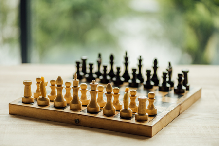 Old chess board set for a new game on the table. Selective focus
