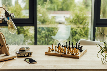 Chess board, vintage camera and smartphone lying