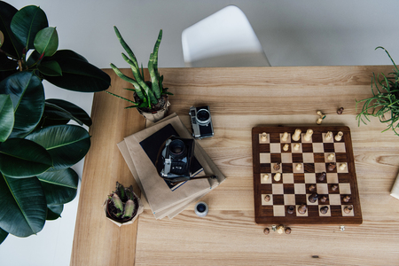 workplace concept with old retro cameras lying on books and chess board during the game Stok Fotoğraf