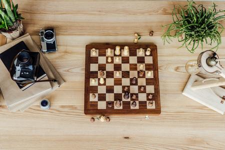 古いビンテージ カメラと木製のテーブルの書籍設定チェス盤