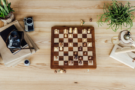 chess board set with old vintage cameras and books on wooden table