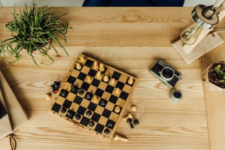 チェスの駒、ヴィンテージカメラ木製テーブルの上の鉢植えとチェス盤
