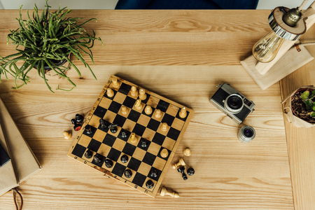 chess board with chess pieces, vintage camera and potted plant on wooden table Stok Fotoğraf